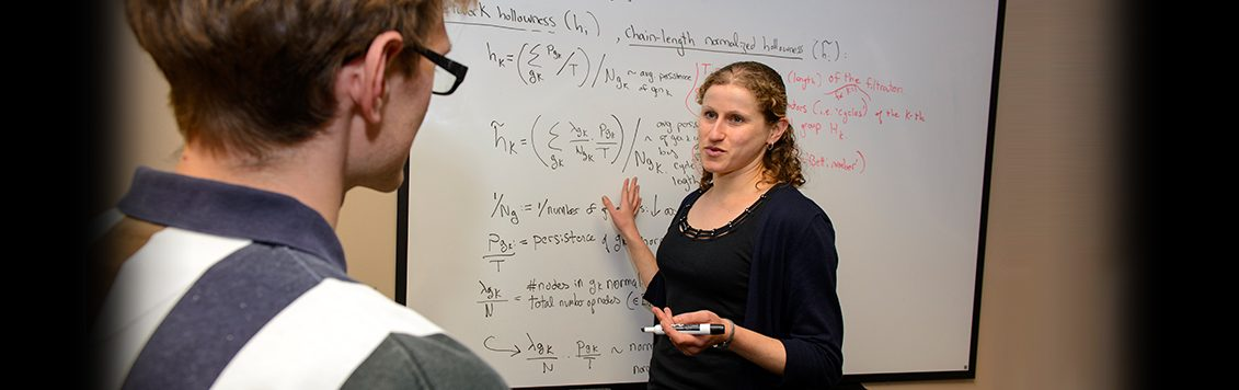 Anna Konstorum explaining an equation to a medical student
