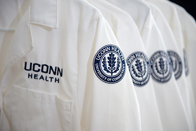 UConn Health lab coats hanging in a row