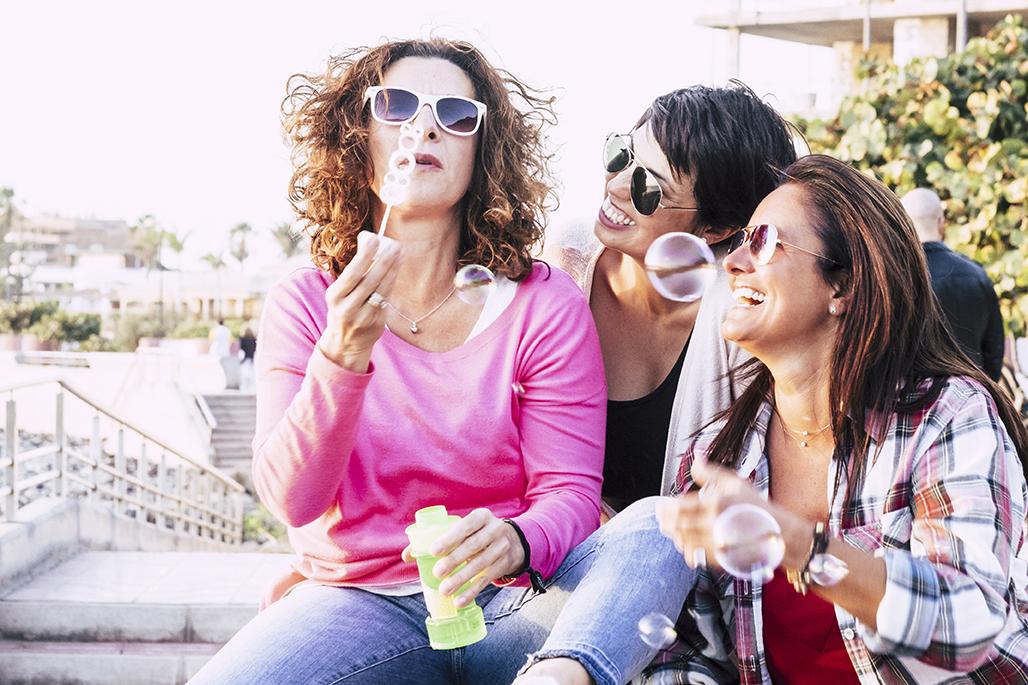Three women outside blowing bubbles