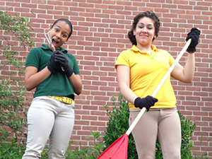 Teens raking and participating in outdoor cleanup