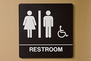 A restroom sign for female, male, and the physically challenged