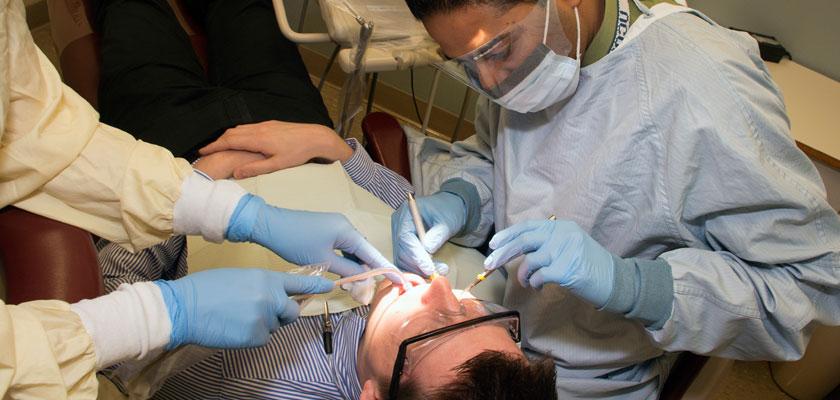 Dr. Avinash Bidra, working a dental patient