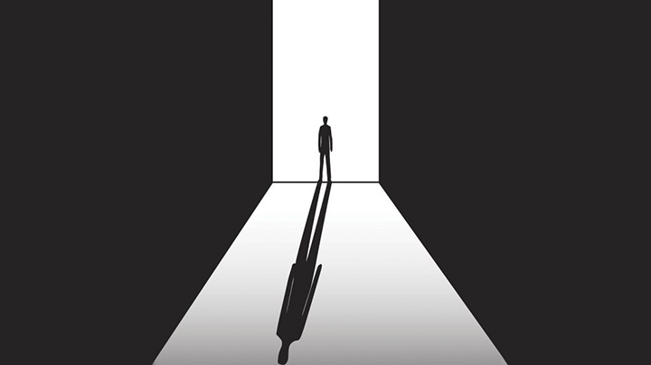 A silhouette of a man stands in a doorway. His shadow stretches out in front of him. (Getty Images)