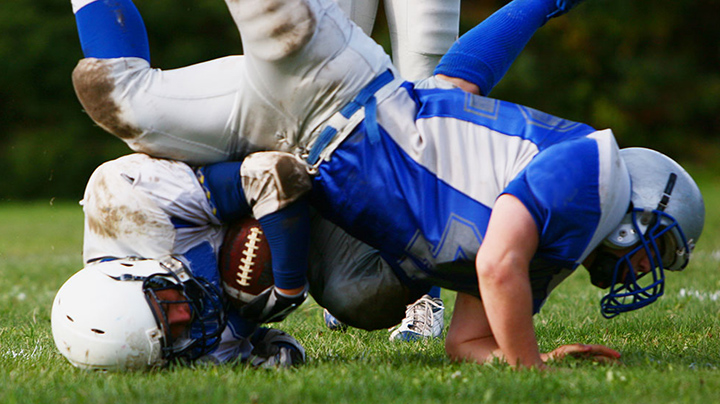 Two football players are falling to the ground after a tackle. One player is landing on his head. (Getty Images)