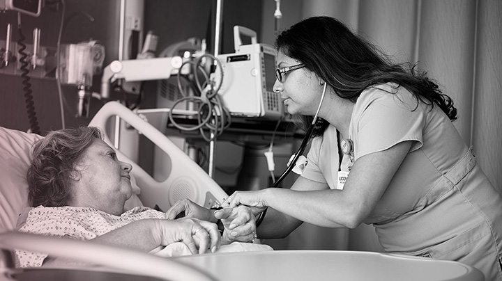 A healthcare professional leans over the bedside of a breast cancer patient.