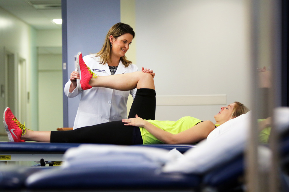 Katherine Coyner MD (right), orthopedic surgeon, works with a patient at the UConn Musculoskeletal Institute at UConn Health in Farmington