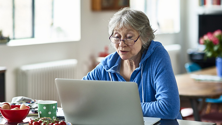 Senior woman wearing glasses using laptop at home