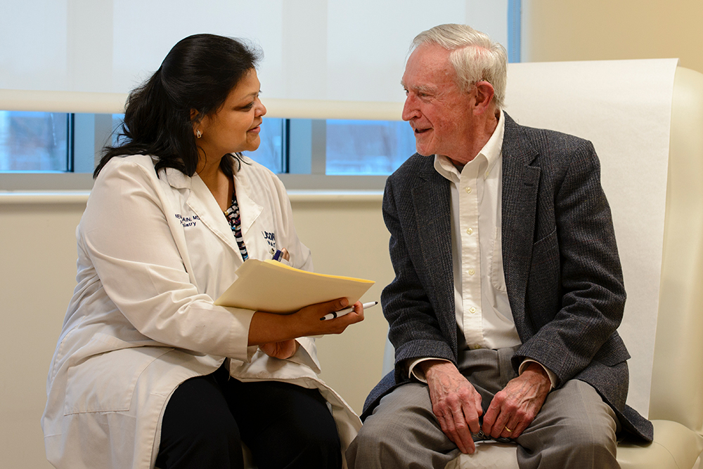 Neha Jain, M.D., talking to a patient in an exam room
