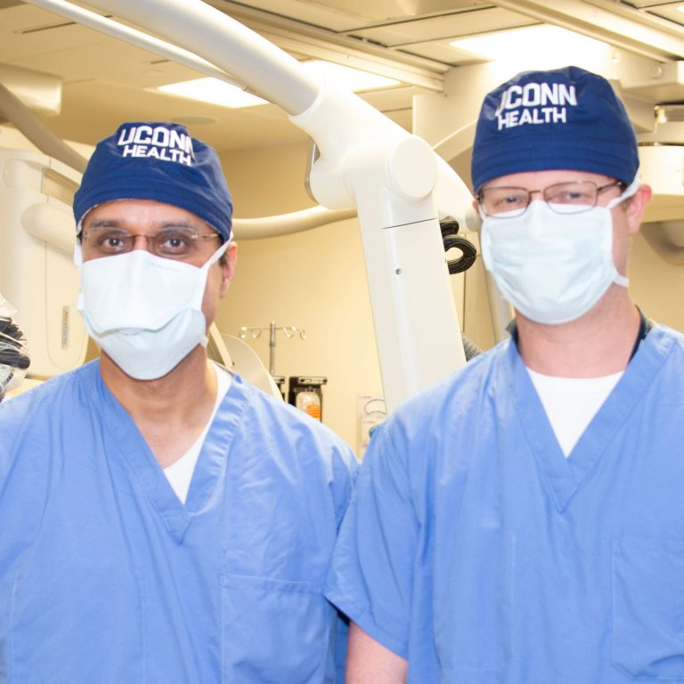 Drs. Ketan Bulsara and Daniel Roberts in surgical masks and scrubs in the operating room