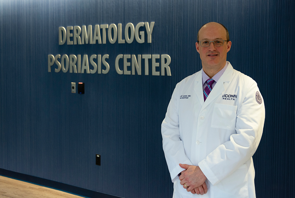 Dr. Philip E. Kerr standing in front of the Psoriasis Center sign