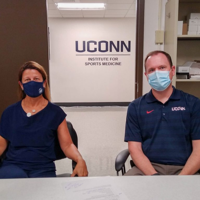 Laurie Devaney and Matt Hall seated in front of UConn Institute for Sports Medicine sign