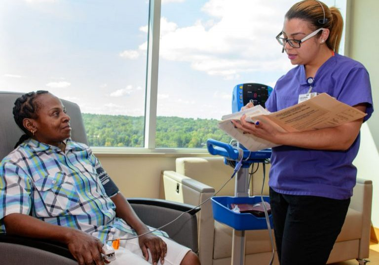 A nurse takes care of a sickle cell patient in the New England Sickle Cell Institute at UConn Health